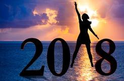 Gelukkige nieuwe jaarkaart 2018 Silhouet van jonge vrouw op de strandtribune als deel van het Nummer 2018 teken met zonsondergang Royalty-vrije Stock Foto