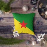 Gelukkige Nieuwjaarmarkering met de vlag van Frans-Guyana op hoofdkussen Het concept van de Kerstmisdecoratie op houten lijst met royalty-vrije stock afbeelding