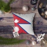 Gelukkige Nieuwjaarmarkering met de vlag van Nepal op hoofdkussen Het concept van de Kerstmisdecoratie op houten lijst met mooie  stock foto's