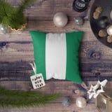 Gelukkige Nieuwjaarmarkering met de vlag van Nigeria op hoofdkussen Het concept van de Kerstmisdecoratie op houten lijst met mooi royalty-vrije stock afbeeldingen
