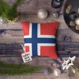 Gelukkige Nieuwjaarmarkering met Svalbard en Jan Mayen-vlag op hoofdkussen Het concept van de Kerstmisdecoratie op houten lijst m royalty-vrije stock foto's