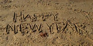 Gelukkige Nieuwjaarwoorden die in Zand worden geschreven Stock Afbeeldingen