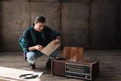 gelukkige nostalgische jonge mens in wijnoogst windcheater met vinyl stock afbeeldingen