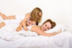 Gelukkige ochtend - vrouw en jonge geitjes op het bed stock afbeeldingen