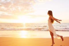 Gelukkige Onbezorgde Vrouw die op het Strand bij Zonsondergang dansen Royalty-vrije Stock Afbeeldingen