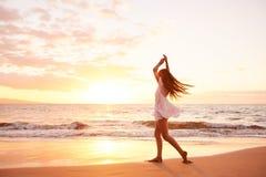 Gelukkige Onbezorgde Vrouw die op het Strand bij Zonsondergang dansen Stock Afbeelding