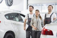 Gelukkige onderhoudsingenieurs die weg in automobiele reparatiewerkplaats kijken Stock Foto