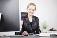 Gelukkige Onderneemster Calculating in haar Worktable royalty-vrije stock foto's