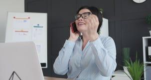 Gelukkige onderneemster die op mobiele telefoon spreken stock video