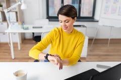 Gelukkige onderneemster die slim horloge met behulp van op kantoor royalty-vrije stock fotografie