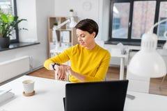 Gelukkige onderneemster die slim horloge met behulp van op kantoor stock foto's