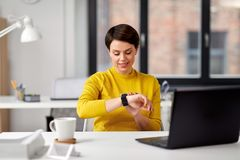 Gelukkige onderneemster die slim horloge met behulp van op kantoor royalty-vrije stock afbeeldingen