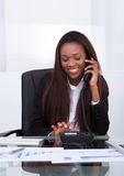 Gelukkige onderneemster die van landline telefoneren Stock Fotografie