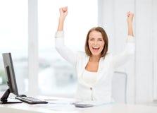 Gelukkige onderneemster met computer in bureau stock foto