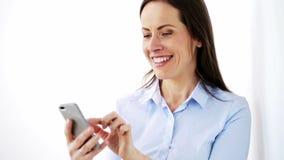Gelukkige onderneemster met smartphone op kantoor stock video