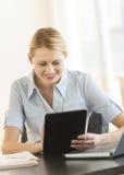 Gelukkige Onderneemster Using Digital Tablet bij Bureau Royalty-vrije Stock Afbeelding