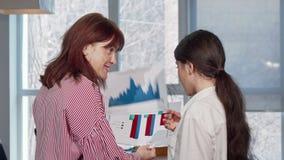 Gelukkige onderneemsters die aan de camera glimlachen, die van het werken genieten op het kantoor stock video