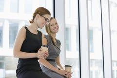 Gelukkige onderneemsters met beschikbare koffiekoppen op kantoor Stock Fotografie