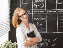 Gelukkige onderneemstervrouw bij schoolraad met programma planning stock foto