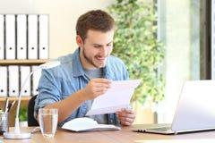 Gelukkige ondernemer die een brief lezen stock afbeeldingen