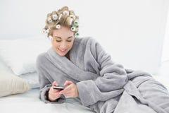 Gelukkige ontspannen blondevrouw in haarkrulspelden die haar mobiele telefoon met behulp van royalty-vrije stock foto's