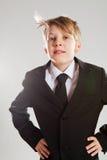 Gelukkige ontspannen jonge jongen in zwart kostuum Royalty-vrije Stock Foto's
