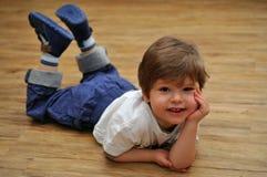 Gelukkige ontspannende kleine jongen die op houten vloer ligt royalty-vrije stock afbeelding