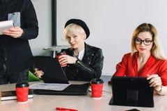 Gelukkige ontwerpers die in hun bureau samenwerken Twee jonge meisjesmedewerkers die bij de lijst zitten en werken tijdens stock afbeelding