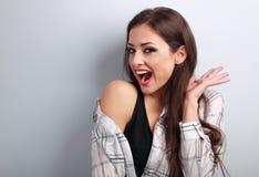 Gelukkige opgewekte jonge vrouw die met open mond op blauwe rug gillen Royalty-vrije Stock Foto's