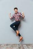 Gelukkige opgewekte vrolijke jonge mens die en het vieren succes springen Royalty-vrije Stock Foto's