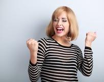 Gelukkige opgewekte winnaar met geopende mond Gelukkige blonde jonge satisf Royalty-vrije Stock Afbeeldingen