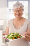 Gelukkige oude dame die verse groene salade houden Royalty-vrije Stock Foto