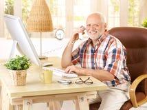 Gelukkige oude mens op landline vraag stock afbeeldingen