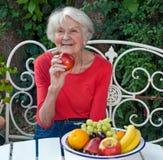 Gelukkige Oude Vrouw bij de Tuinlijst met Vruchten Royalty-vrije Stock Foto