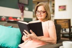 Gelukkige oude vrouw die haar favoriet boek lezen Royalty-vrije Stock Foto
