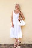 Gelukkige oudere vrouw in de lentekleding die zich met beurs bevinden stock foto