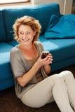 Gelukkige oudere vrouw die thuis koffiemok houden stock foto's