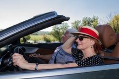Gelukkige oudere vrouw met een zonhoed en haar partner in een luxe convertibele auto stock foto's