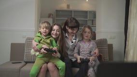 Gelukkige oudere zusters en blije jongere jonge geitjes die op de laag het spelen videospelletjes in de logeerkamer zitten Pretfa stock footage