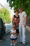 Gelukkige ouders dichtbij een nieuwe auto en kind hier Stock Afbeelding