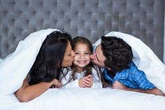 Gelukkige ouders die dochter kussen Royalty-vrije Stock Afbeelding