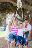 Gelukkige ouders die hun kinderen op een schommeling duwen Royalty-vrije Stock Afbeelding