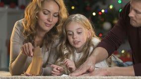 Gelukkige ouders die leuk meisje met brief helpen aan Santa Claus, geloof in mirakel stock footage