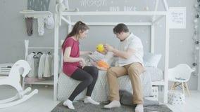 Gelukkige ouders die met zuigelingsmeisje spelen in slaapkamer stock videobeelden