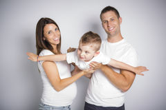 Gelukkige ouders die vliegtuig met hun die kindjongen spelen op witte achtergrond wordt geïsoleerd stock afbeelding