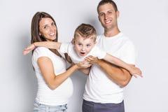 Gelukkige ouders die vliegtuig met hun die kindjongen spelen op witte achtergrond wordt geïsoleerd stock foto's