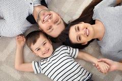 Gelukkige ouders en hun zoon die samen op vloer liggen Familietijd royalty-vrije stock foto's