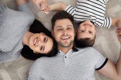 Gelukkige ouders en hun zoon die samen op vloer liggen Familietijd royalty-vrije stock afbeelding