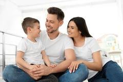 Gelukkige ouders en hun zoonszitting samen op vloer Familietijd royalty-vrije stock afbeeldingen