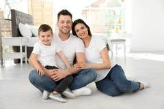 Gelukkige ouders en hun zoonszitting samen op vloer Familietijd royalty-vrije stock fotografie